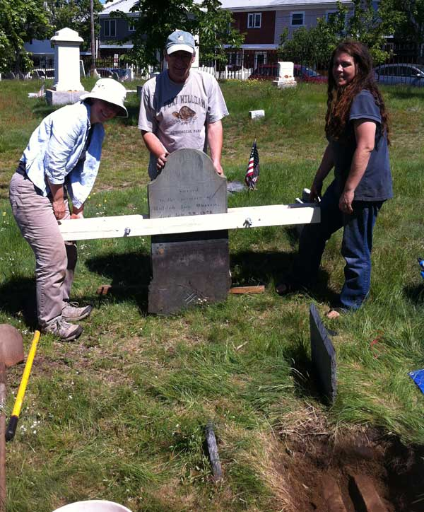 Preparing to move a gravestone into place