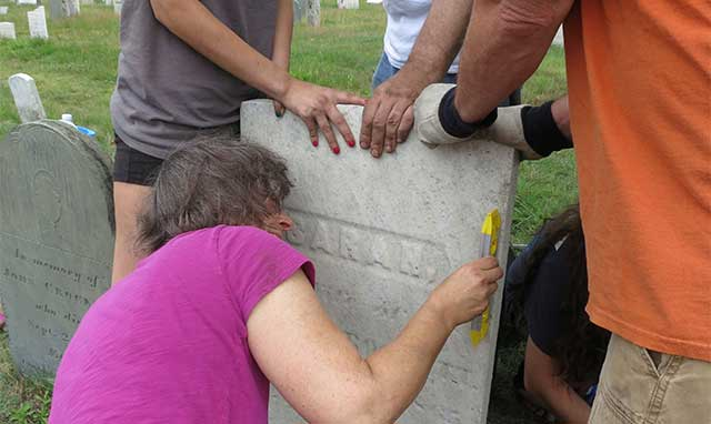 conservation team levels a gravestone