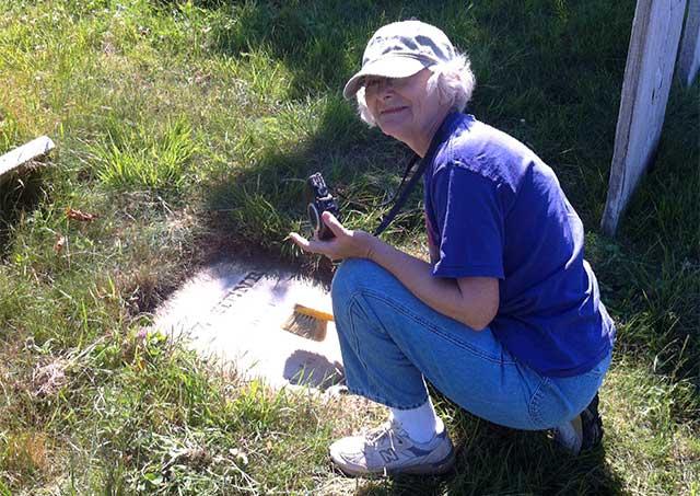 sharon brushes a gravestone